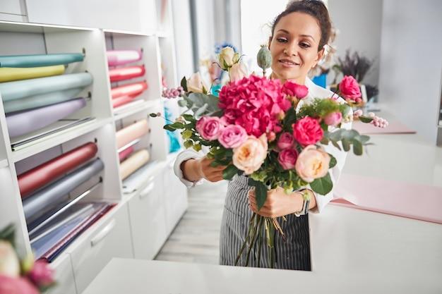 그녀가 만든 꽃다발을 들고 있는 숙련된 꽃 전문가