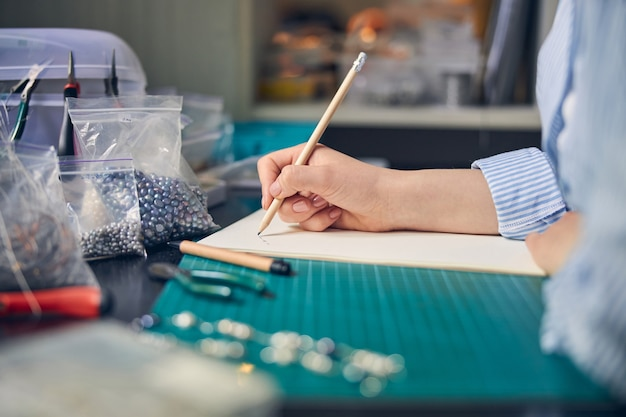 Опытный ювелирный работник с помощью карандаша создает эскиз ожерелья на бумаге.