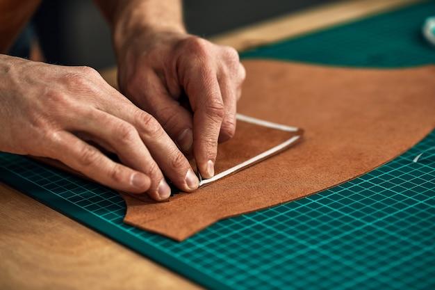 숙련된 가죽 제조 작업자가 일부 샘플을 절단합니다. 클로즈업 샷