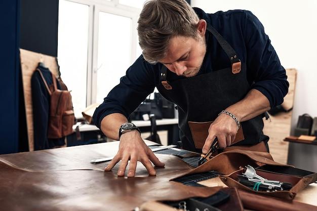 熟練した皮革製造労働者がいくつかのサンプルをカットしています。