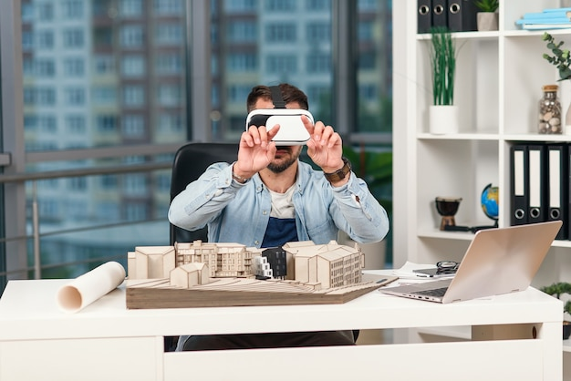 디자인 국에서 증강 현실 안경으로 건축 프로젝트를 검토하는 숙련 된 남성 건축가