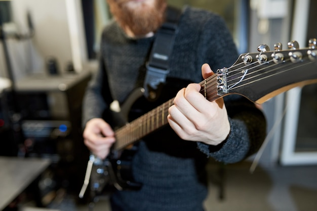 Квалифицированный мужчина играет на электрогитаре в студии