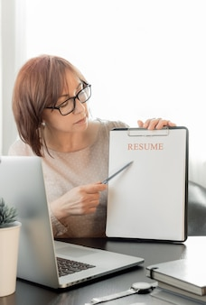 Skilled middle aged woman communicating online, distance studying or working in recruitment office.