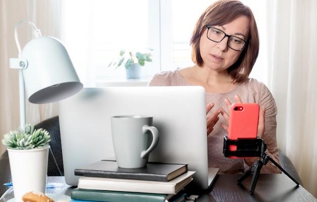Квалифицированная женщина средних лет общается онлайн или обучается дистанционно по телефону на штативе,
