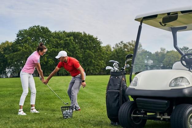 선글라스를 쓴 젊은 여성에게 골프 클럽을 올바르게 잡도록 가르치는 숙련 된 개인 코치