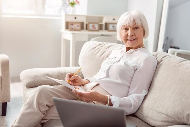 熟練したプロ。ソファに座って、ビジネスプロジェクトに取り組んでいる間、市場調査を行っている間ポーズをとっている明るい年配の女性