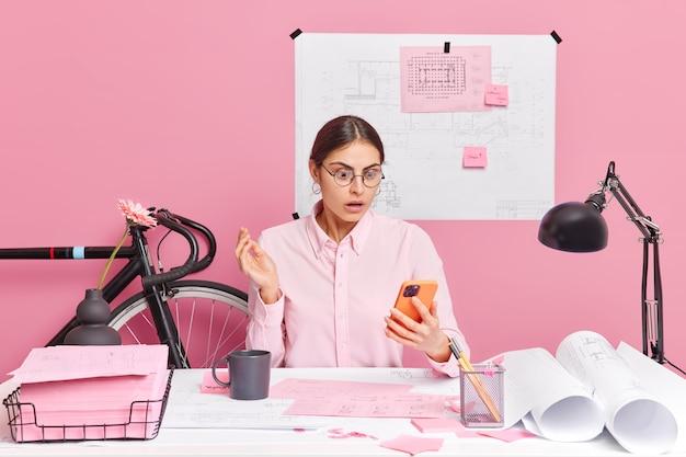 衝撃的な表情でスマートフォンのディスプレイに集中する熟練したプロの女性エンジニアが、デスクトップで設計図のポーズを作成します
