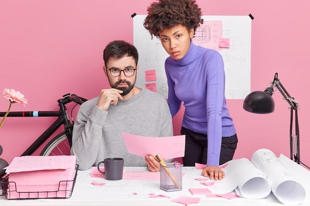 Professionisti qualificati, donne e uomini, impiegati d'ufficio, condividono opinioni e cercano soluzioni, studiano documenti, sviluppano un progetto architettonico durante la collaborazione, posano nello spazio di coworking, hanno espressioni serie