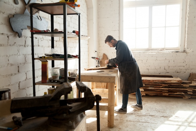 Skilled self-employed carpenter working with wood in carpentry workshop interior