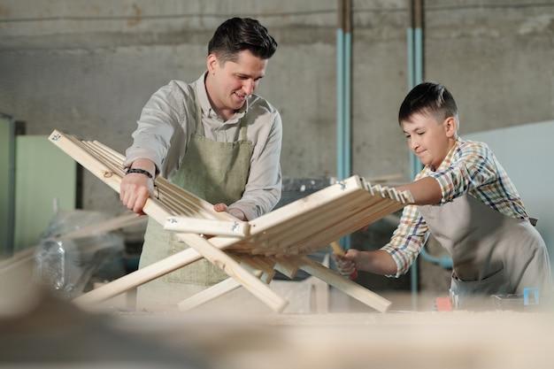 家具のワークショップで父親が開催した椅子に最後のタックを打つ熟練した10代の少年