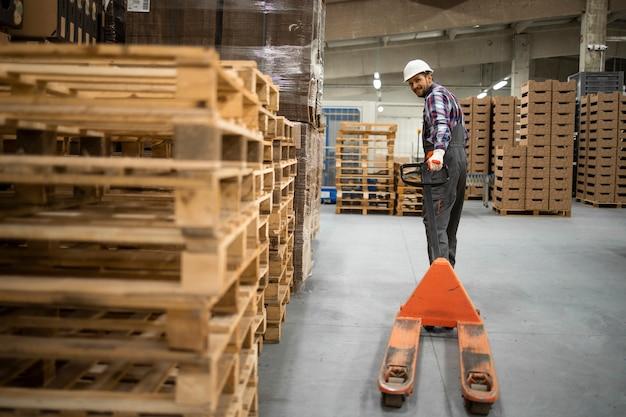 熟練した倉庫の従業員が手動フォークリフトを操作し、工場の保管室で働いています。
