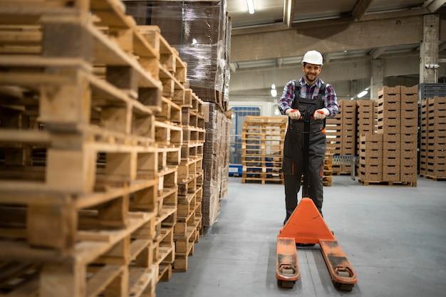 숙련 된 창고 직원이 수동 팔레트 잭을 밀고 공장 보관실에서 일하고 있습니다.
