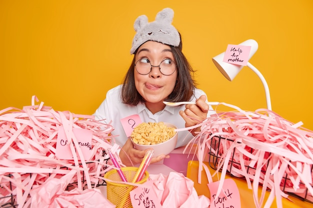 Skilled woman works freelance from home has delicious breakfast holds bowl with cereals wears spectacles for vision correction sleepmask ready to work on creative task isolated over yellow wall