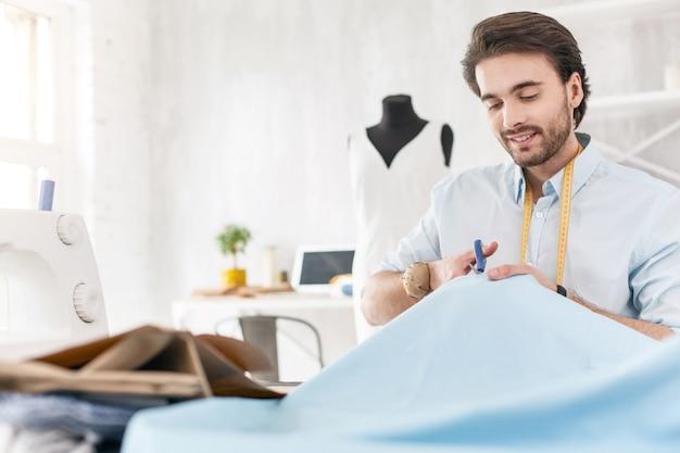 숙련공. 쾌활한 남성 양장점 웃고 그의 새 드레스 작업