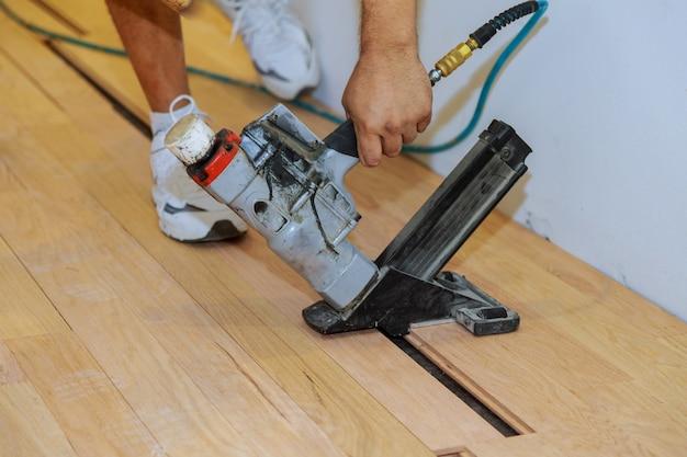 Skilled worker during the installation of prefinished interlocking parquet.
