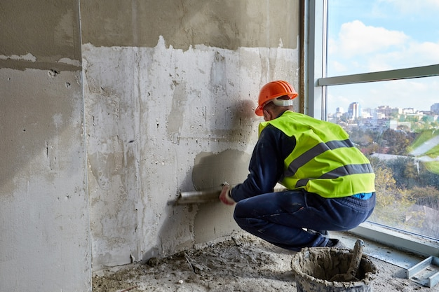 Skilled worker in working clothes and orange hard hat is putting putty on the wall using spatula flat of a building under construction