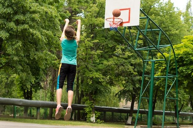 ゴールを撃つ熟練した若いバスケットボール選手