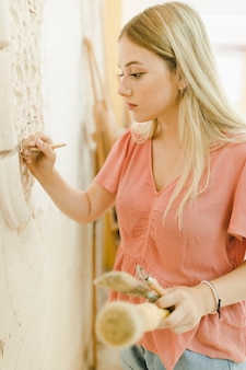 Skilled young woman carving on wall with tools