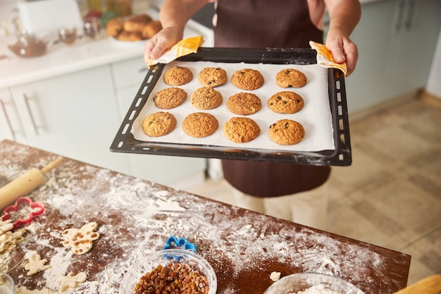 신선한 핫 쿠키와 함께 트레이를 제시하는 숙련된 제빵사