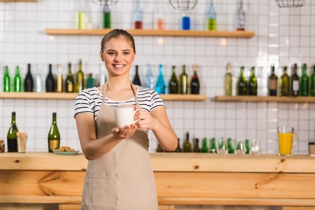 巧みなバリスタ。カフェでバリスタとして働いている間、笑顔であなたを見ている陽気な素敵なポジティブな女性