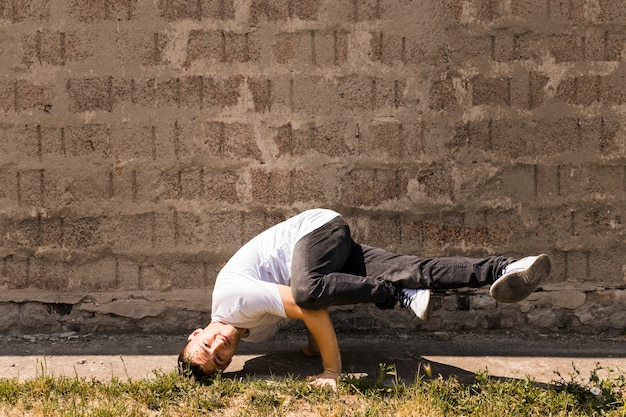 Умелый танцор, выступающий против каменной стены