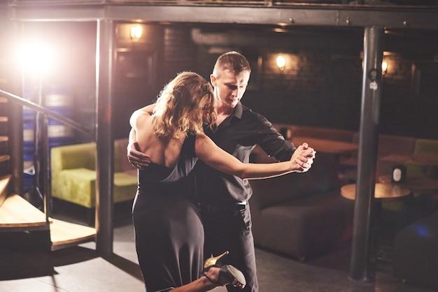 光の下で暗い部屋で演奏する熟練したダンサー。