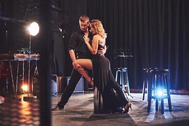 Умелые танцоры выступают в темной комнате при свете.