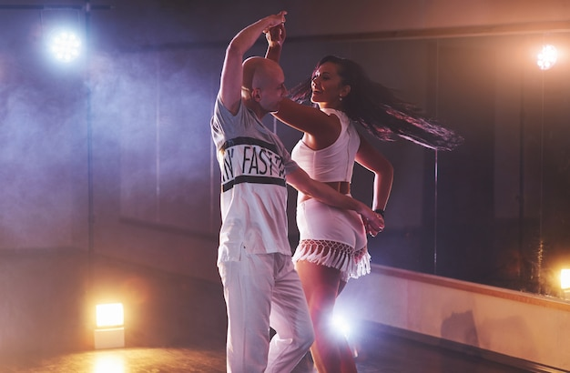 Умелые танцоры выступают в темной комнате под концертным светом и дымом. чувственная пара исполняет художественный и эмоциональный современный танец