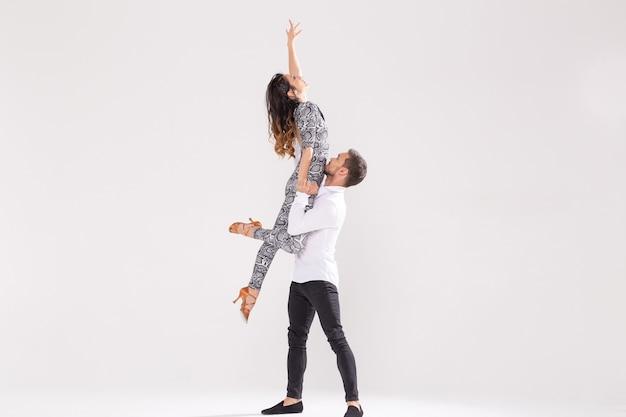 Умелые танцоры выступают на белом фоне с копией пространства. чувственная пара, исполняющая артистичный и эмоциональный современный танец