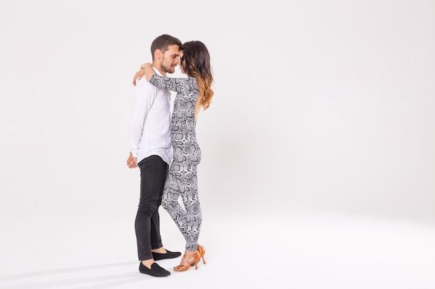 コピースペースのある白い壁で踊る上手なダンサー。芸術的で感情的なコンテンポラリーダンスを実行する官能的なカップル