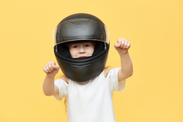 Умелая опытная маленькая девочка в защитном мотоциклетном шлеме