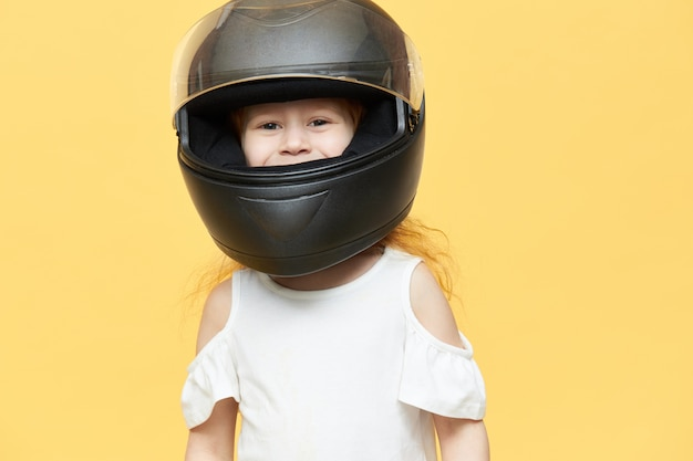 Skillful experienced little girl in safety motorcycle helmet
