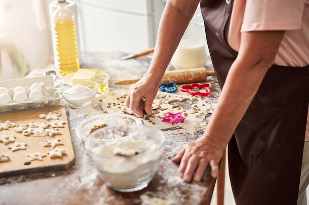 Skillful female baker making sorting out dough for cookies