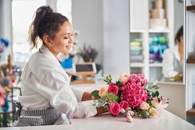 Умелый флорист женщина любуясь букетом цветов