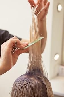Опытный парикмахер, стригущий волосы клиента в салоне красоты