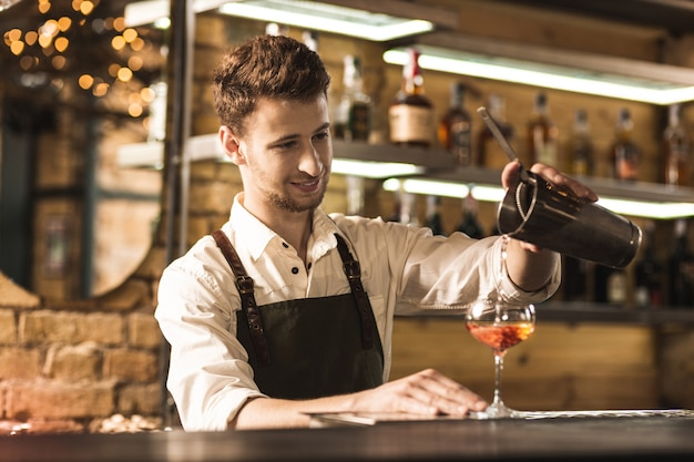 Skillful worker. charming young barman standing at the bar counter and pouring a cocktail into the glass