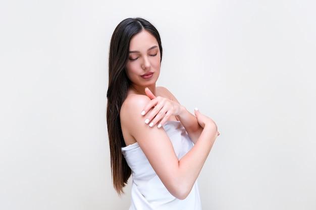 スキンケアとボディケア。タオルを着た美しい若い女性が手で肌に触れます。