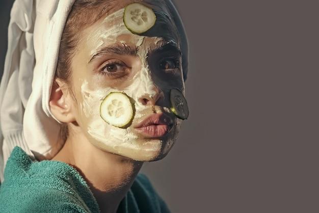 スキンケアとヘアケアスパウェルネス化粧品美容皮膚科ビューティーサロンのコンセプト頭にキュウリマスクタオルを付けた女の子または女性の顔