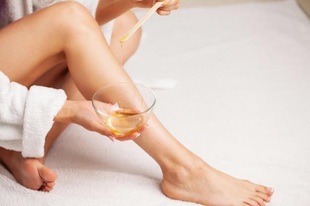 Уход за кожей, женщина наносит воск на ногу, чтобы удалить волосы