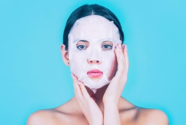 スキンケアと美容のコンセプト。保湿マスク。アンチエイジング手順。青い背景に、彼女の顔にシートマスクを適用する女性。マスクを持つ美しい女性。