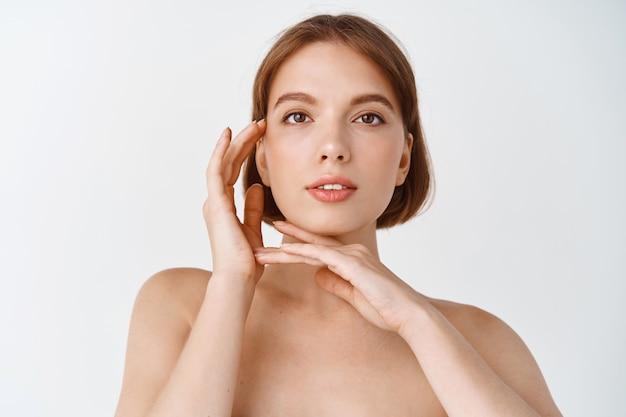 피부 관리 및 미용. 벌거벗은 채 빛나는 얼굴을 만지고 있는 자연의 젊은 여성. 스킨케어 제품 효과를 보여주는 소녀, 흠 없는 깨끗한 피부, 흰 벽