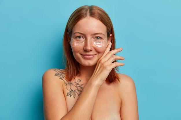 피부 관리 및 미용 절차. 만족스러운 주근깨가있는 여성은 얼굴을 부드럽게 만지고, 하이드로 겔 눈 패치를 착용하고, 알몸으로 서 있으며, 매력적인 미소로 완벽하게 관리되는 몸매를가집니다. 무료 사진