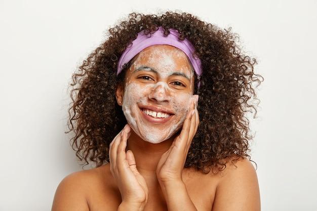 피부 관리 및 민족성 개념. 아름다운 만족 곱슬 여자는 얼굴을 씻고, 피부에 거품이 있고, 행복하게 보이며, 흰 벽에 토플리스를 서고, 신선함과 청결을 즐깁니다.