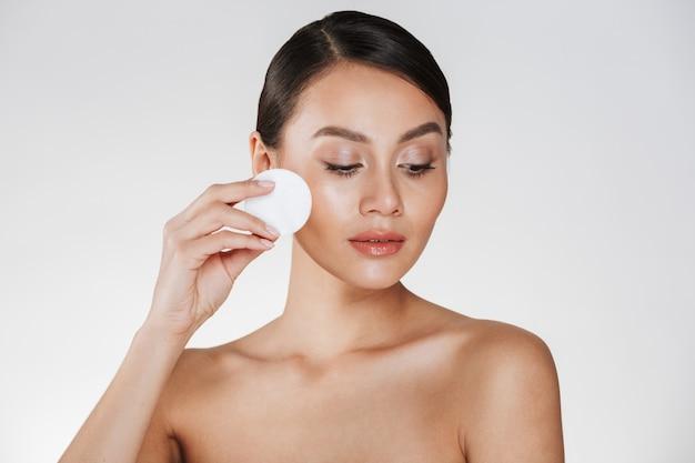 Уход за кожей и здоровое лечение женщины, снимающей макияж с лица с ватным тампоном, изолированным на белом