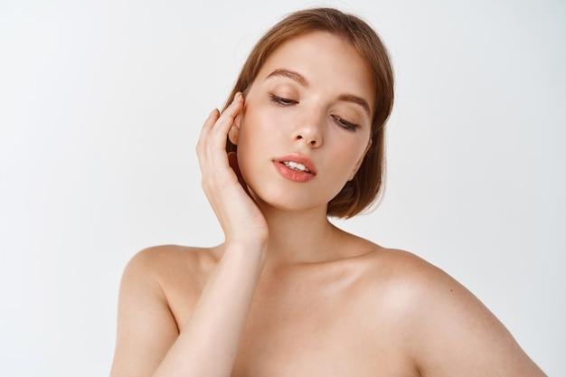 Уход за кожей и женская красота. нежная молодая женщина с обнаженными плечами, касаясь натуральной кожи лица без макияжа, наносит косметику ежедневного ухода, чувственно стоя на белой стене