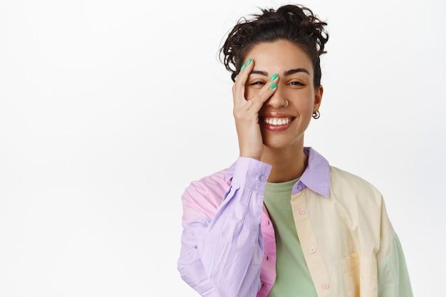 Уход за кожей и концепция женщин. красивая молодая женщина с естественной кожей без макияжа, касающаяся чистого чистого лица, улыбающаяся и смеющаяся на белом