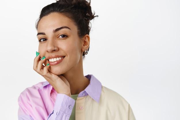 スキンケアと女性のコンセプト。きれいな自然な肌、化粧なし、白い歯の笑顔、頬に触れ、白で満足しているように見える若い魅力的な女性