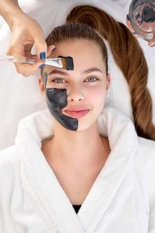 피부 관리, 미용사는 매력적인 젊은 여성에게 검은색 얼굴 마스크 크림을 바르고 있습니다.