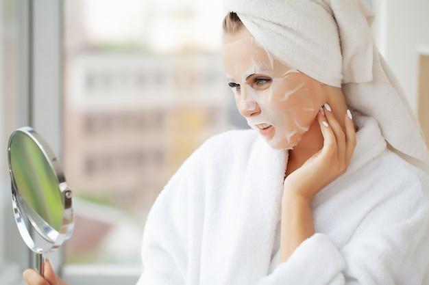 Уход за кожей, красивая женщина с лицевой маской в салоне красоты.