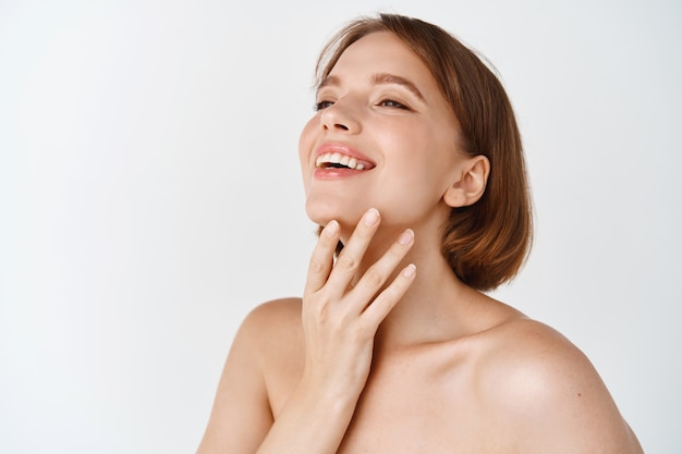 Skin care beauty. beautiful natural woman touching neck and smiling, looking aside. girl laughing and showing glowing, hydrated facial skin, standing on white wall